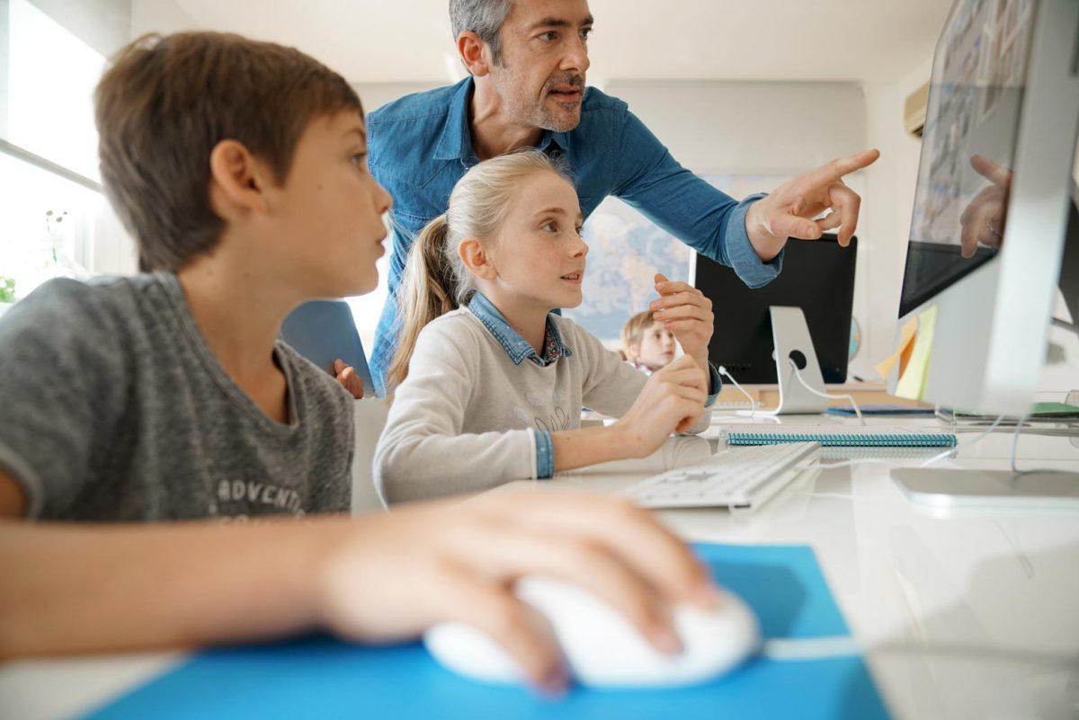 Lehrer mit Schülern an Computern